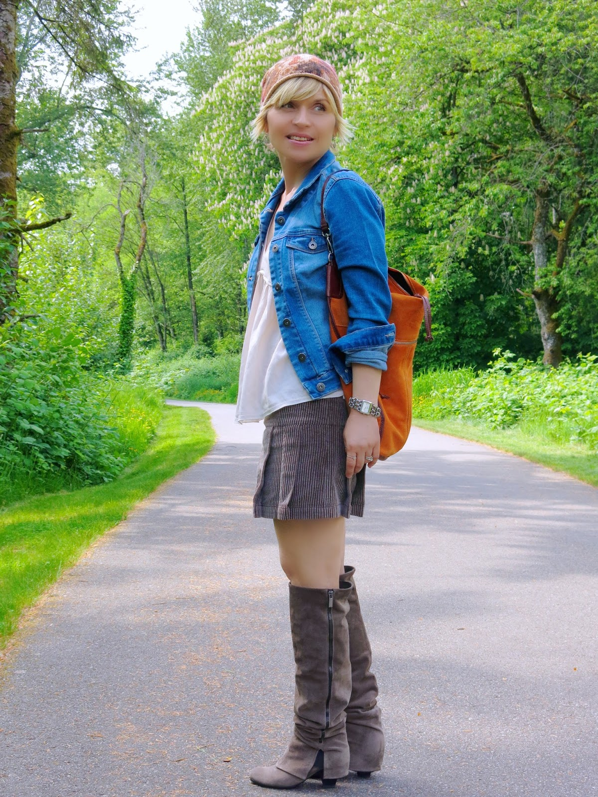 styling a corduroy mini-skirt with suede boots, a denim jacket, and a beanie