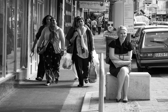A young woman sits waiting for a bus while another group of women pass by laughing