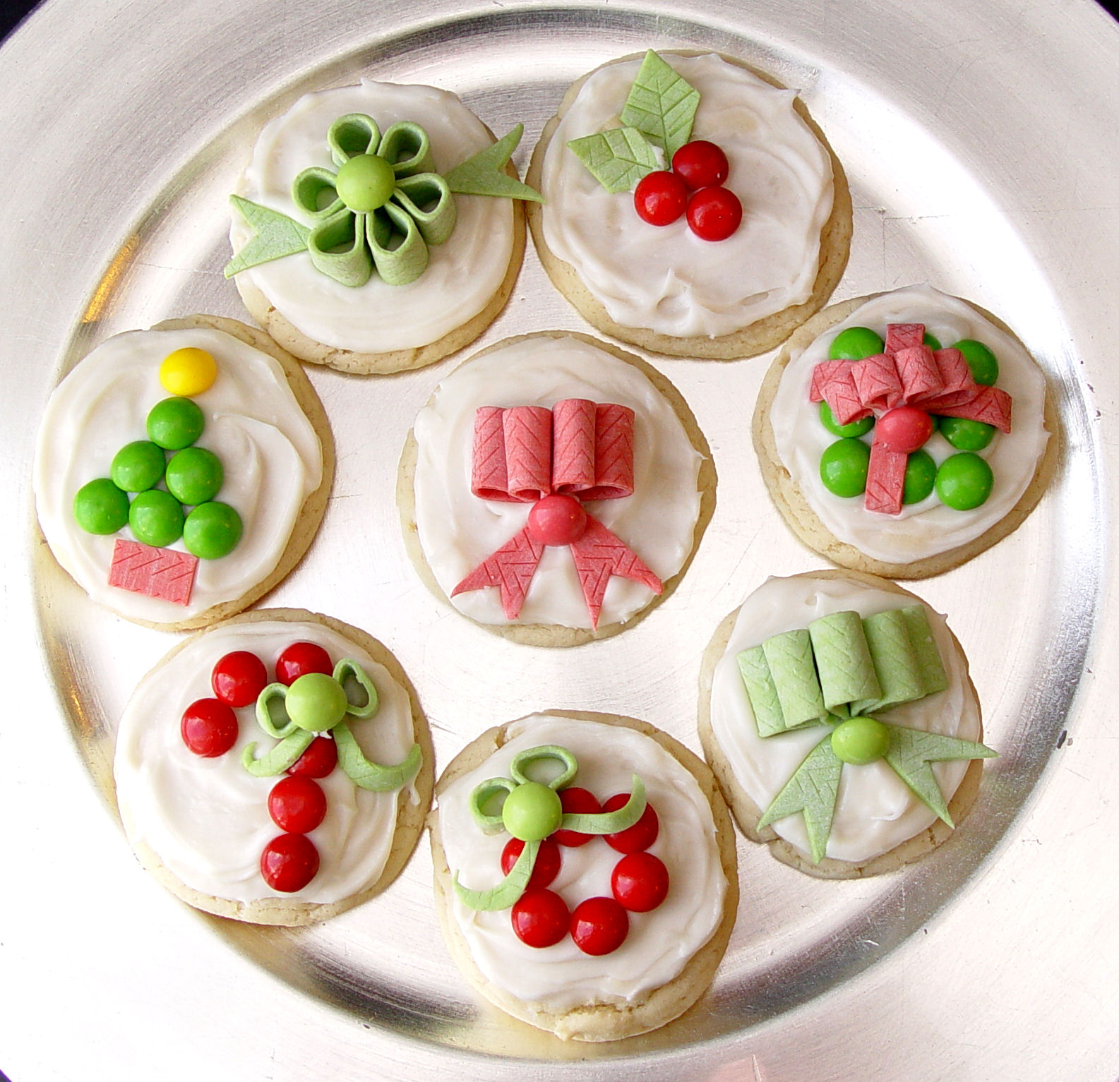 and there you have it cut some streamers out of the gum and tuck them into the loops put a little bit of frosting on a skittle and stick it in front of - Decorated Christmas Sugar Cookies