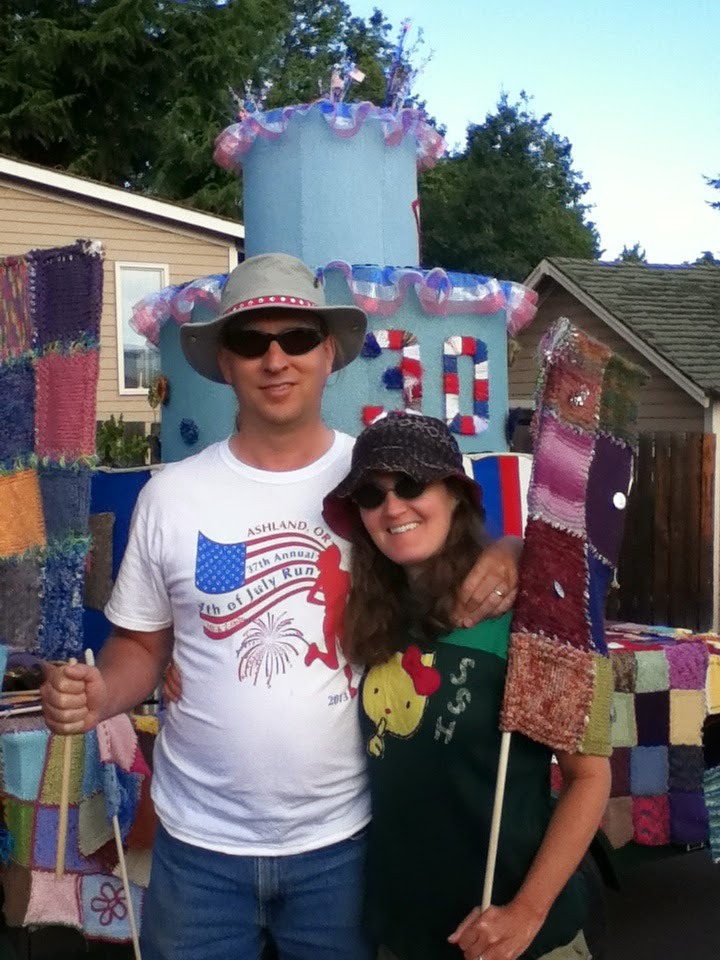 Jonathan Donihue and Cynthia Parkhill holding flags assembled from knit swatches in front of a kniting-covered, circular layer-cake frame on a flatbed trailer