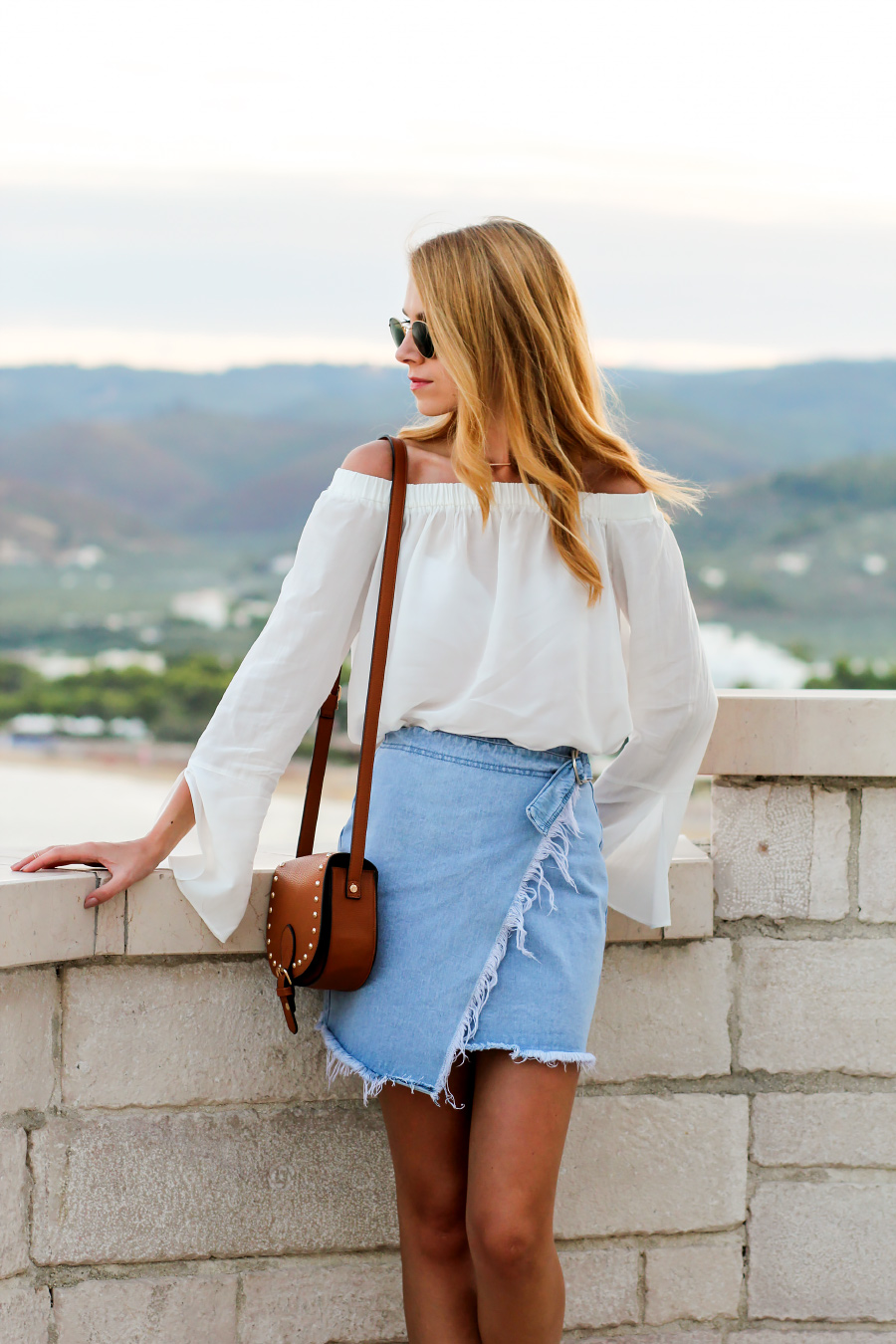 off-the-shoulder blouse with distressed denim skirt and tan bag