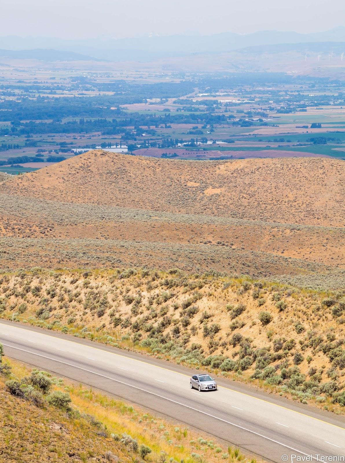 Дорога, проходящая между пустынных холмов. Очень американский пейзаж.