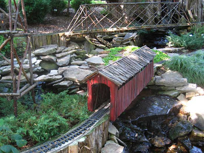 Red covered bridge made of rough pieces of wood