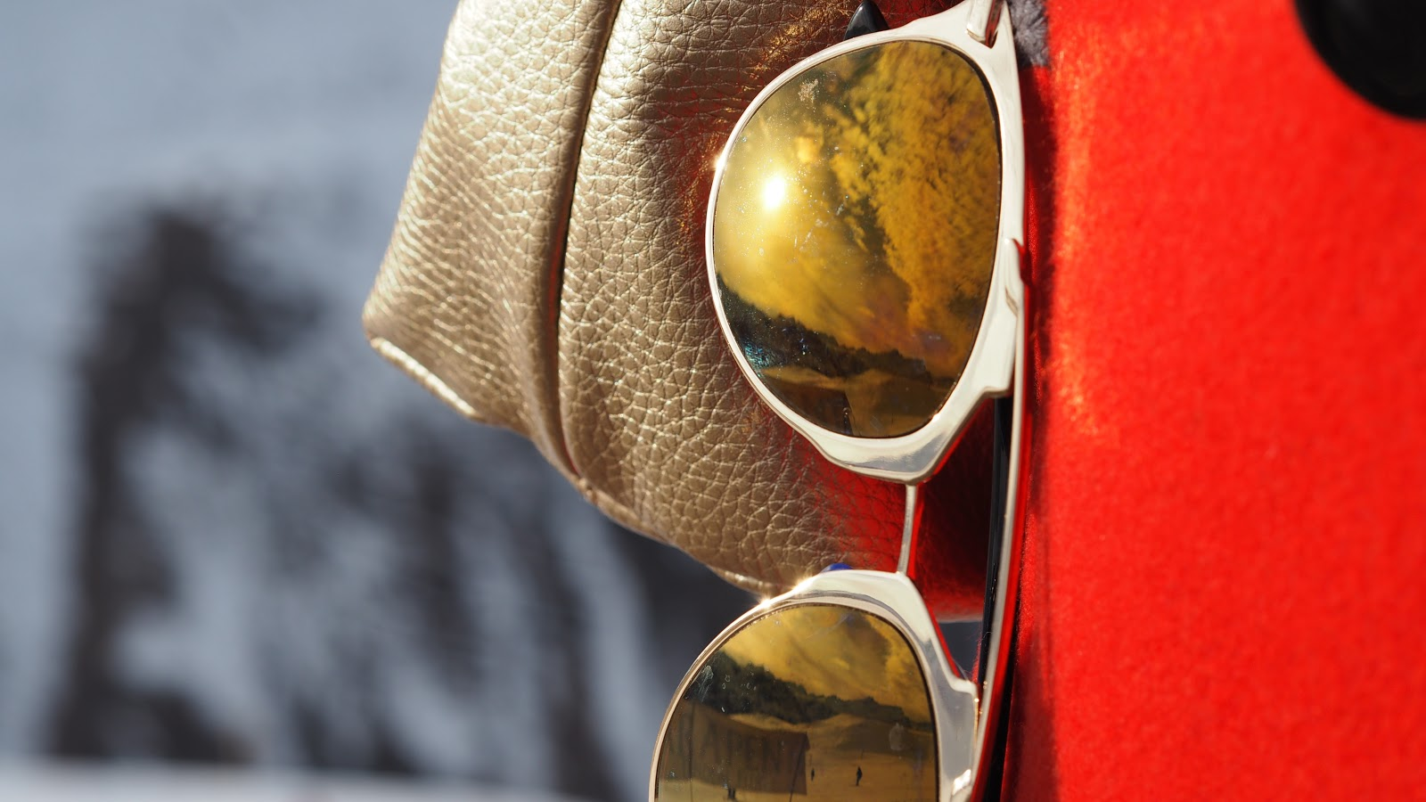 Sunglasses and gold bag against red coat, Val d'Isere, France