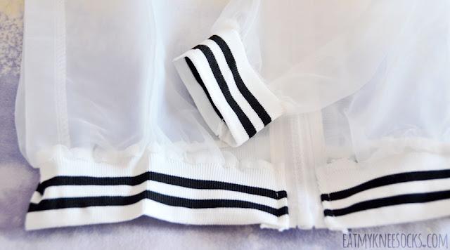 Close-up on the striped hem and sleeve detailing on Dresslink's sheer bomber jacket.