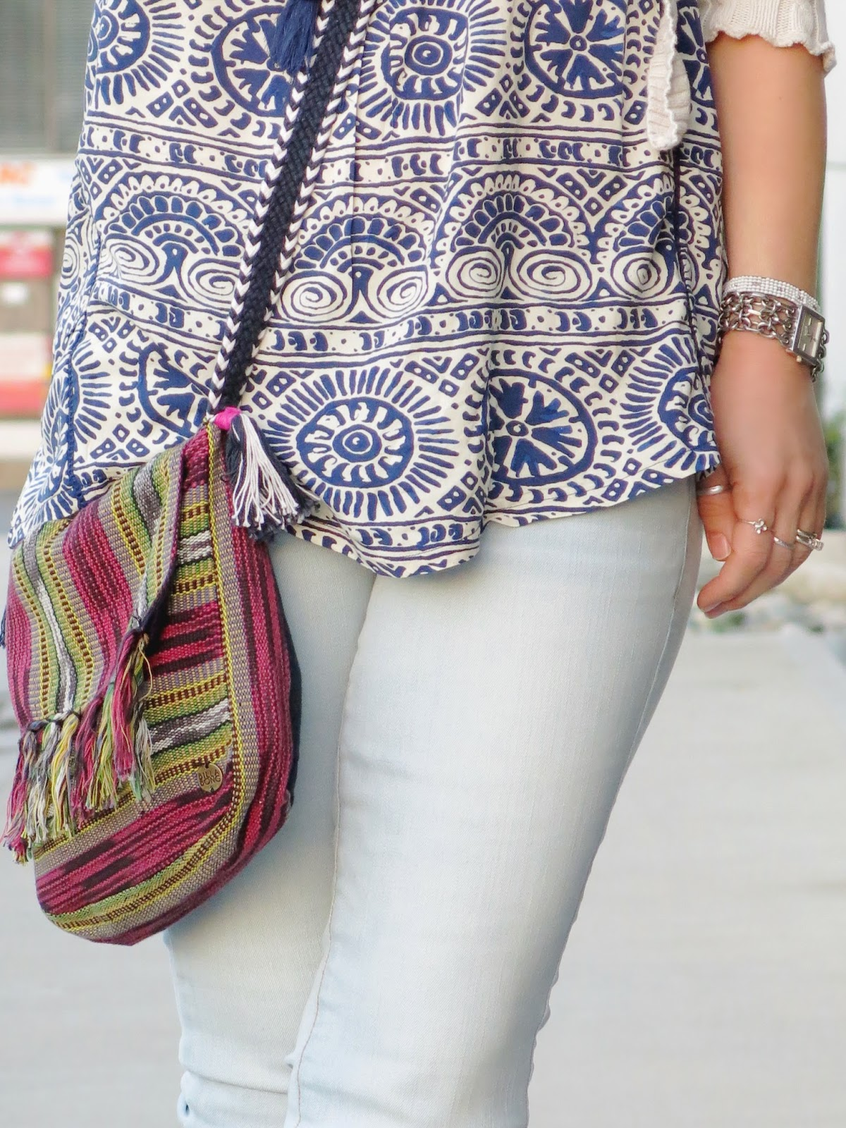 styling bleached skinny jeans with a peasant-style tank top and woven crossbody bag