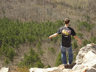 A man standing a the edge of a cliff and below is a woodland forest