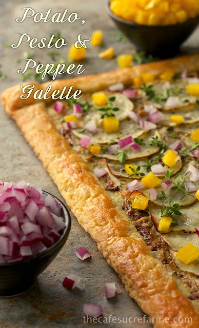 Photo of a Potato Pesto Pepper Galette on a tan stone surface with bowls of diced red onion and yellow bell pepper surrounding the galette.