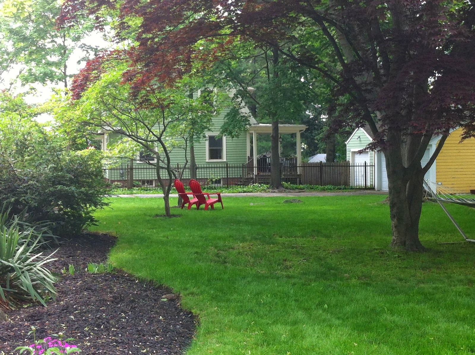 Red adirondack chairs in Providence yard