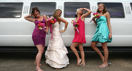 A bride and 3 bridesmaids poses in front of Chicago stretch SUV