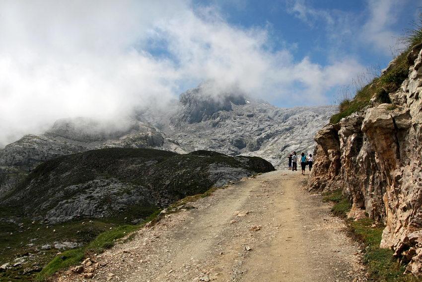 Cimo da montanha com um pico mais alto ao fundo e o nevoeiro a descer. Estrada de terra com algumas pessoas a caminharem.