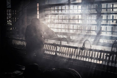 A shot from the Mill showing a boy working on a cotton spinning machine, the air is full of dust and fluff and the sunlight beaming through the window just shows how dingy the factory really is.