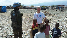 Cite Soleil, Haiti 2011: DWC Participant Cam Grant with the UN Worker and children