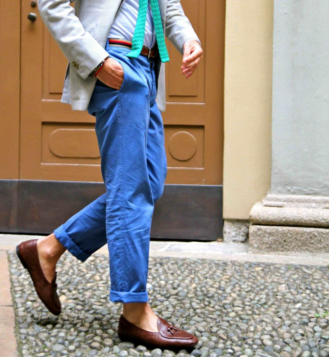 Personally, I think navy chinos are deceptively difficult to pair with. I find that a shirt with a different shade of blue usually looks good, with brown shoes/belt/watch. White shirts work with anything, and I think a charcoal shirt or sweater looks good too.