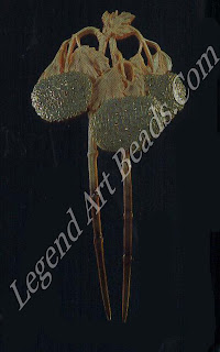 A guelder rose haircomb of horn, gold, enamel and diamonds (c. 1902-03). The patented horn is carved with softly hanging leaves and three heavy snowball-shaped plants.