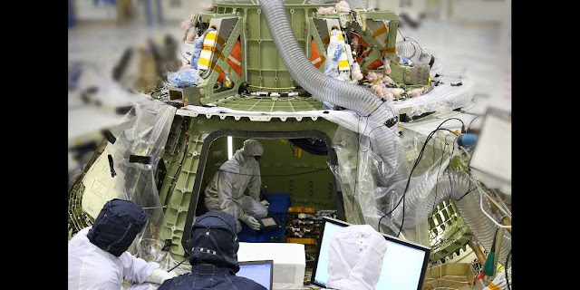 Technicians work inside the Orion crew module being built at Kennedy Space Center to prepare it for its first power on. Turning the avionics system inside the capsule on for the first time marks a major milestone in Orion's final year of preparations before its first mission, Exploration Flight Test Image Credit: Lockheed Martin