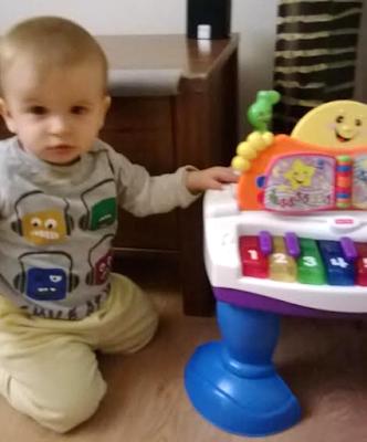 Oyuncak piyanosu başındaki bebek