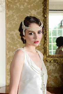 Flapper girl in a 1920's style drop waist bridal gown with a pearl hairband, marcel waves in her hair and 1920's style makeup
