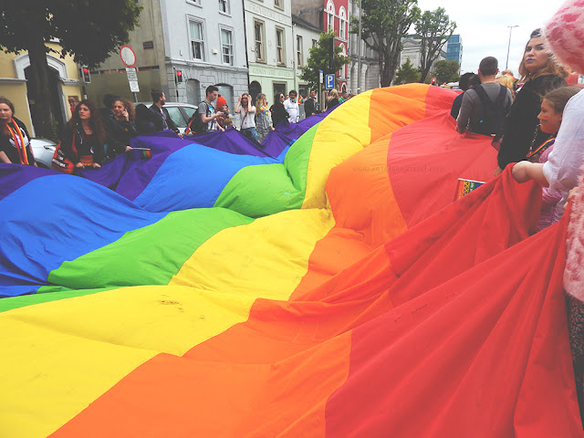 giant rainbow lgbti flag held by many people
