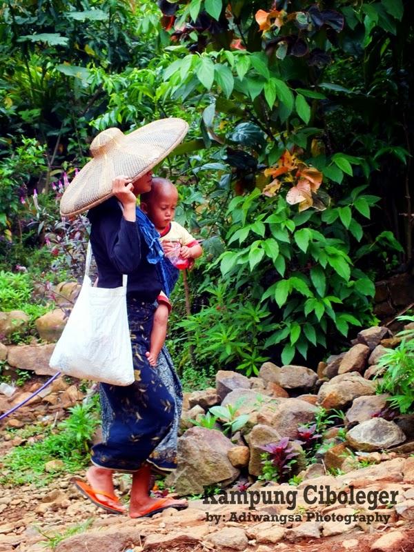 Seorang ibu dari suku Baduy sedang menggendong anaknya