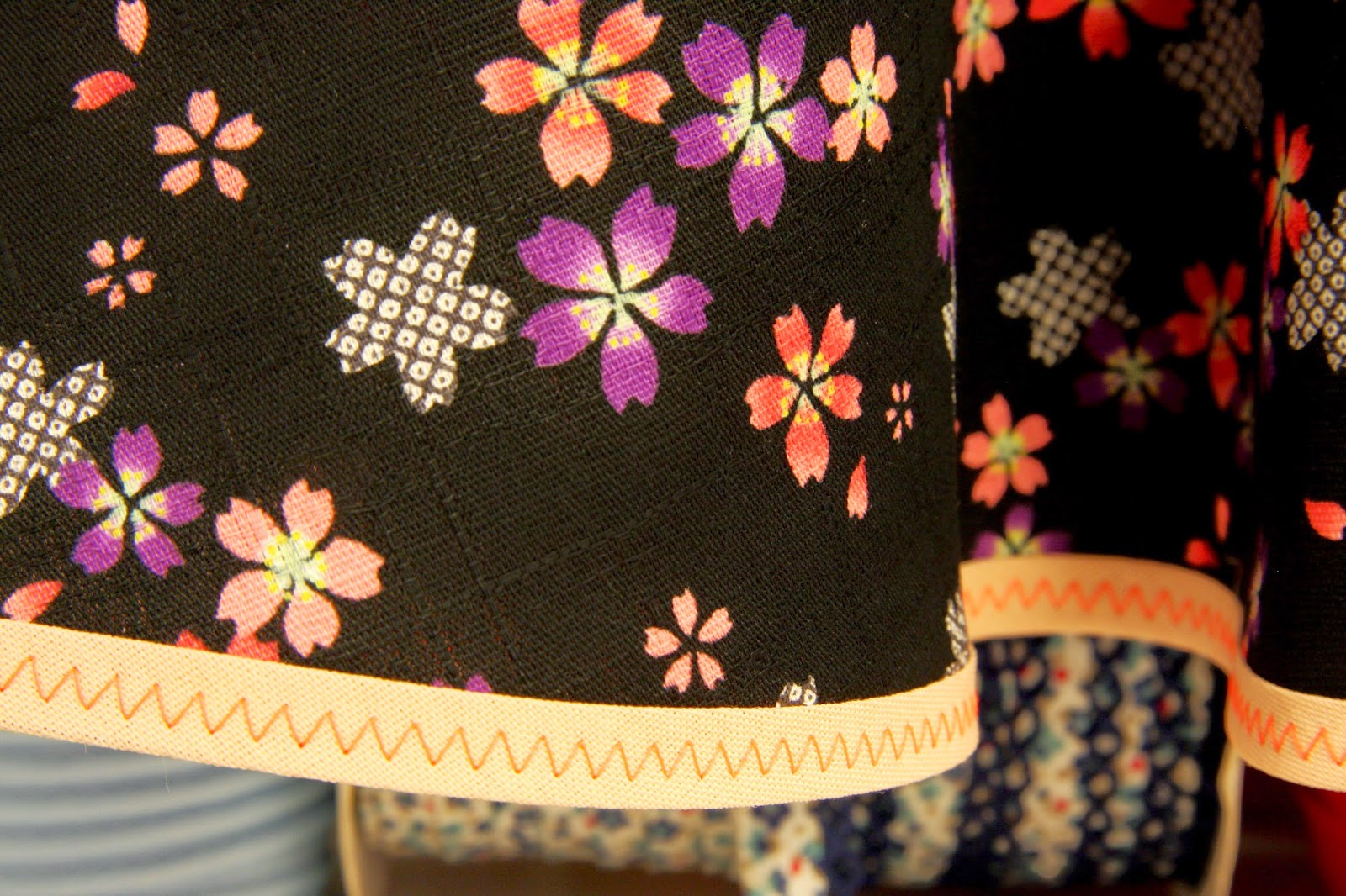 Nederdelen er kantet med laksefarvet skråbånd som har fået zigzag pyntestikning med neonsytråd.