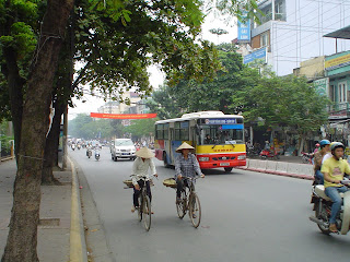 Women on bicycle with Vietnamese hat
