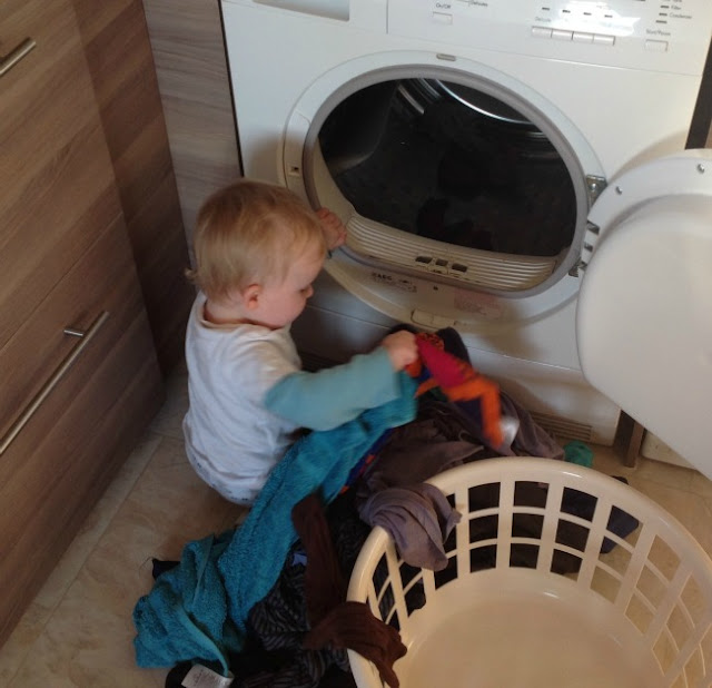 Baby sat on floor emptying tumble dryer