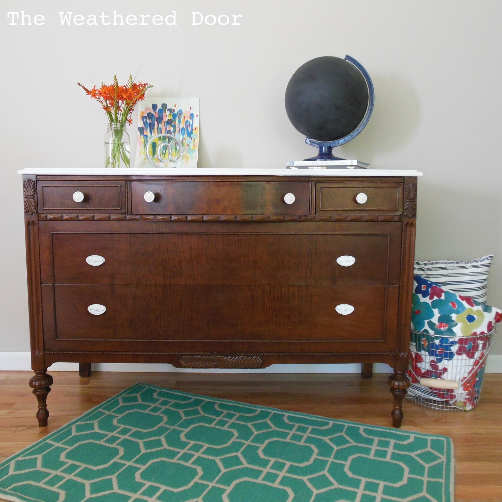 A Dark Wood Dresser With A White Top The Weathered Door