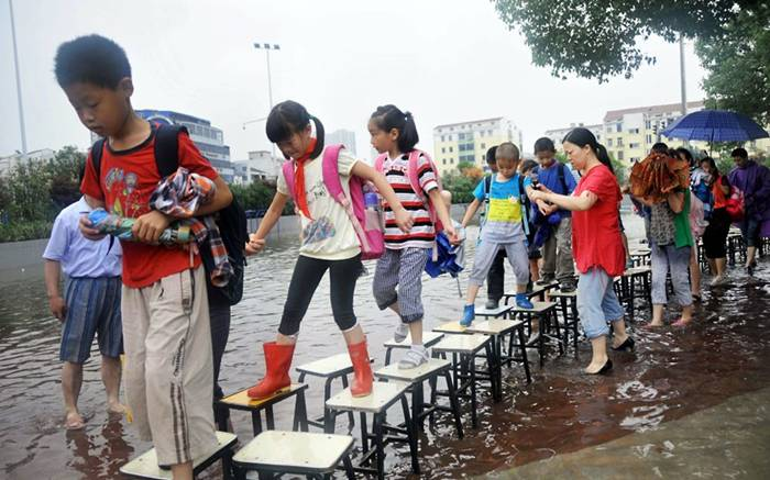 Children walk to school using a 'bridge' made from stools after fl00ding in Changzhou city, Jiangsu Province, ChinaPicture: Quirky China News / Rex Features