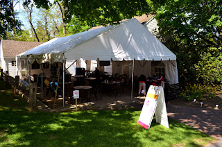 Magnolias outdoor cafe at Heritage with diners under a tent and a sign.