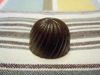 Praline au chocolat noir fourrée à la crème fraiche vanillée