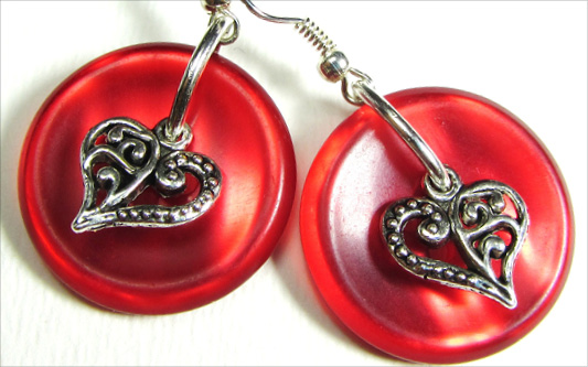 Drop dangle earrings have silver heart charms layered over shiny red buttons