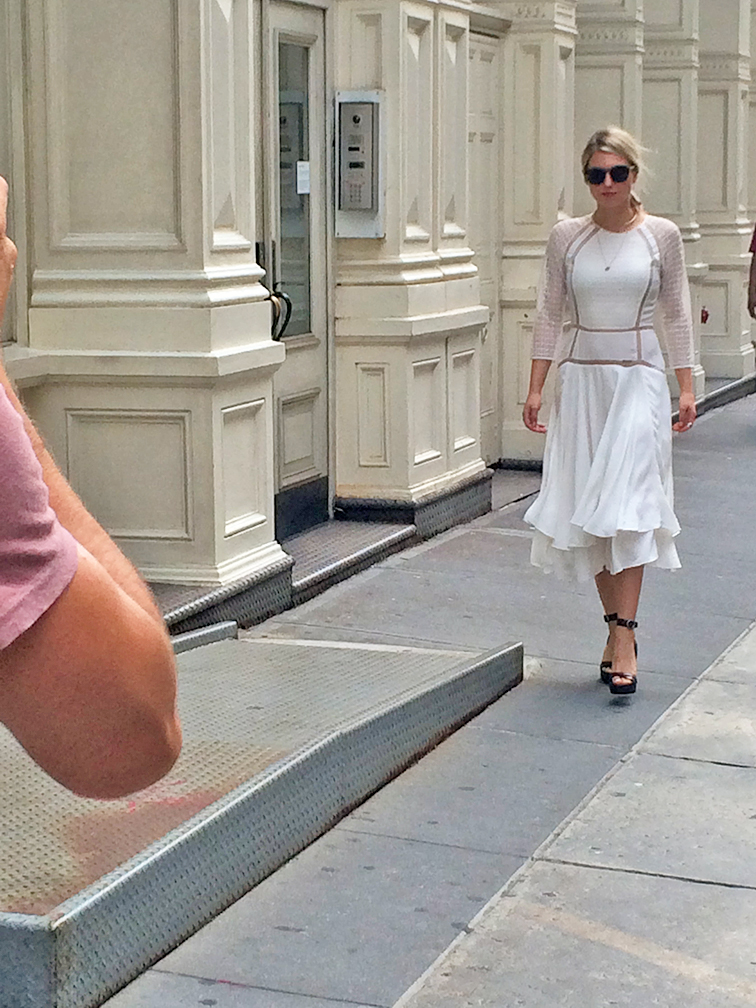 Street Style action shot, on the street in Soho, Hélène Heath from Fashion Over Reason in a white Rebecca Taylor flowy dress, Michael Kors brown leather stacked heels