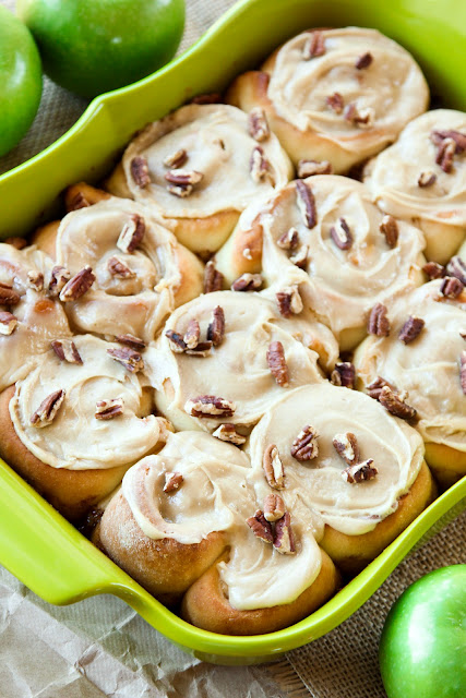 A 9x13 dish full of cinnamon apple rolls topped with pecans