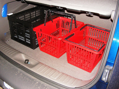 black collapsible crate (left) next to red browsing baskets sold by Demco library supply in back of car