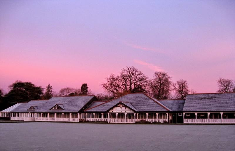 Red dawn sky over frosty bowling greens and clubhouse