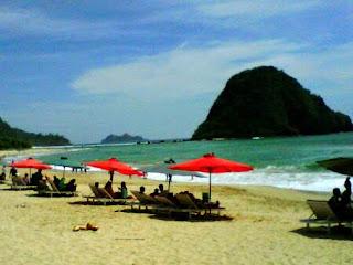 berjemur di pantai pulau merah