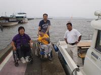 船長と参加者でモーターボートと霞ヶ浦をバックに記念撮影