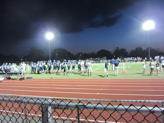 Photo of the football team on the field with the dark clouds looming.