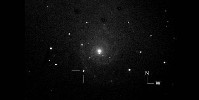 One of the first photos of the possible new supernova (at tick marks) in the nearby galaxy M74 taken by the Italian Supernova Search Project. The object is located 93″ east and 135″ south of the galaxy's center. Credit: Fabio Martinelli