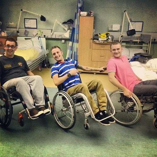 Three men in manual wheelchairs, in a side by side line, all doing wheelies