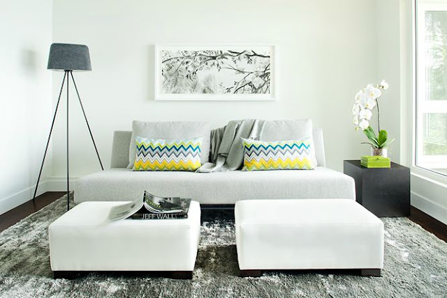 Modern living room with grey sofa with two matching ottomans, dark wood floors, accent pillows with Missoni-esque zig zag pattern in yellow, green, grey and  white, a block side table and a modern style lamp