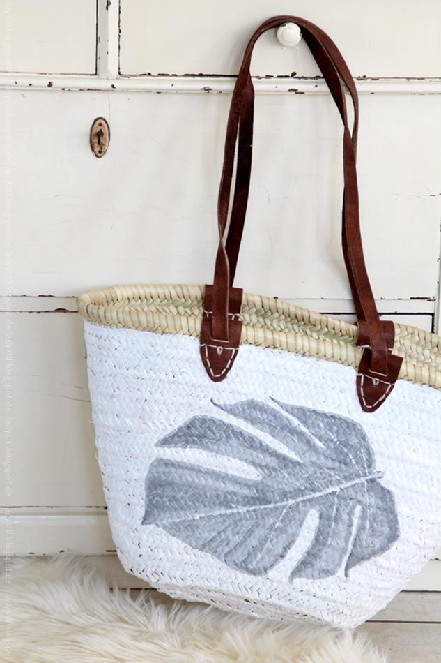 Korbtasche mit aufgemaltem monsterablatt hängt an einer beigen Shabbykommode