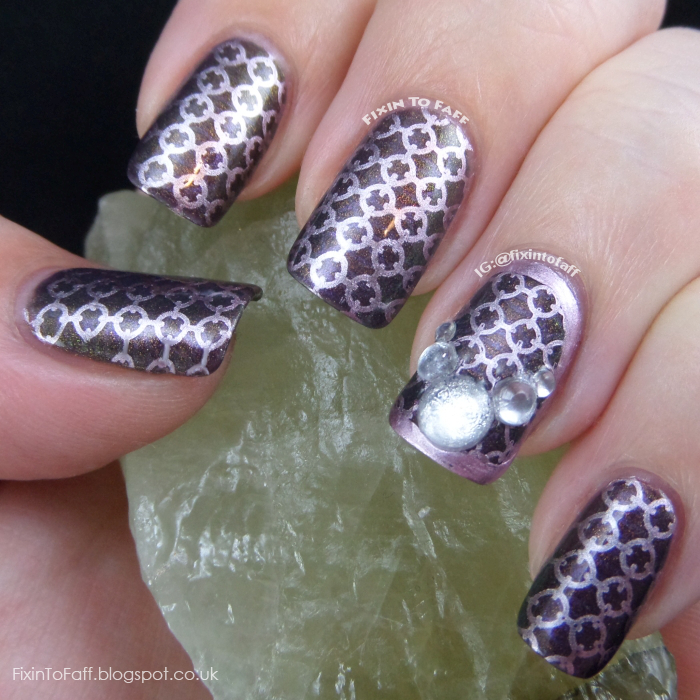 Nail art using a unique quatrefoil pattern design, stamped in lavender chrome finish over a shimmery purple base.
