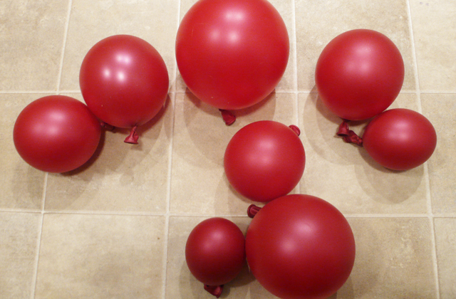 A cluster of red balloons on the floor waiting to be used as props.