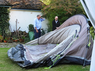 The tent appears to have collapsed. J has his hand to his head.