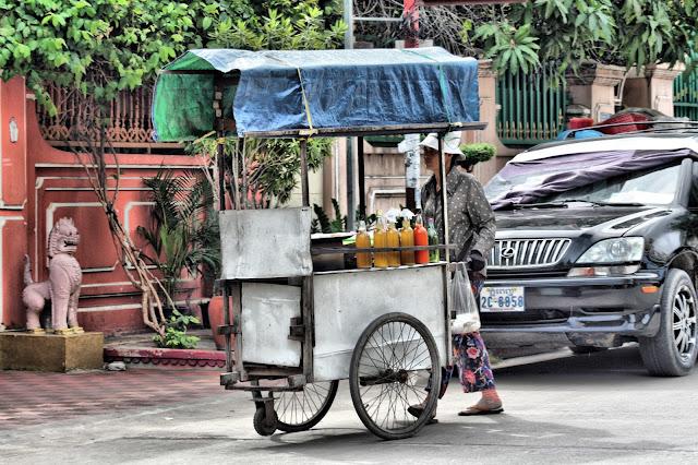 Clichés de la vie quotidienne dans les rues de Phnom Penh. Avec les marchands ambulants, les restaurants de rue, la nouvelle génération de débits de boissons un peu trop colorées et un peu trop sucrées et, enfin, les vendeurs de pain à bicyclette. Album Photo par C. Gargiulo. KiamProd + 855 087 261 019...