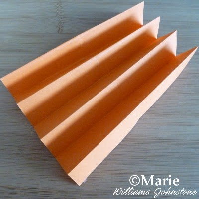 Orange color paper which has been folded in a concertina accordion fold