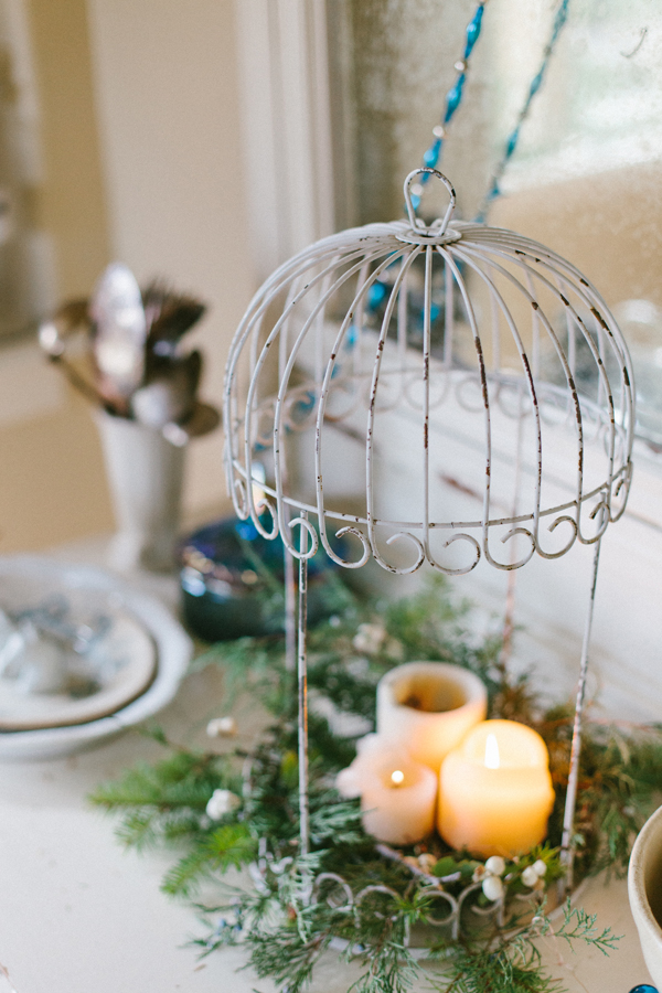 Vintage birdcage with candles & greenery at www.vintagewhitesblog.com