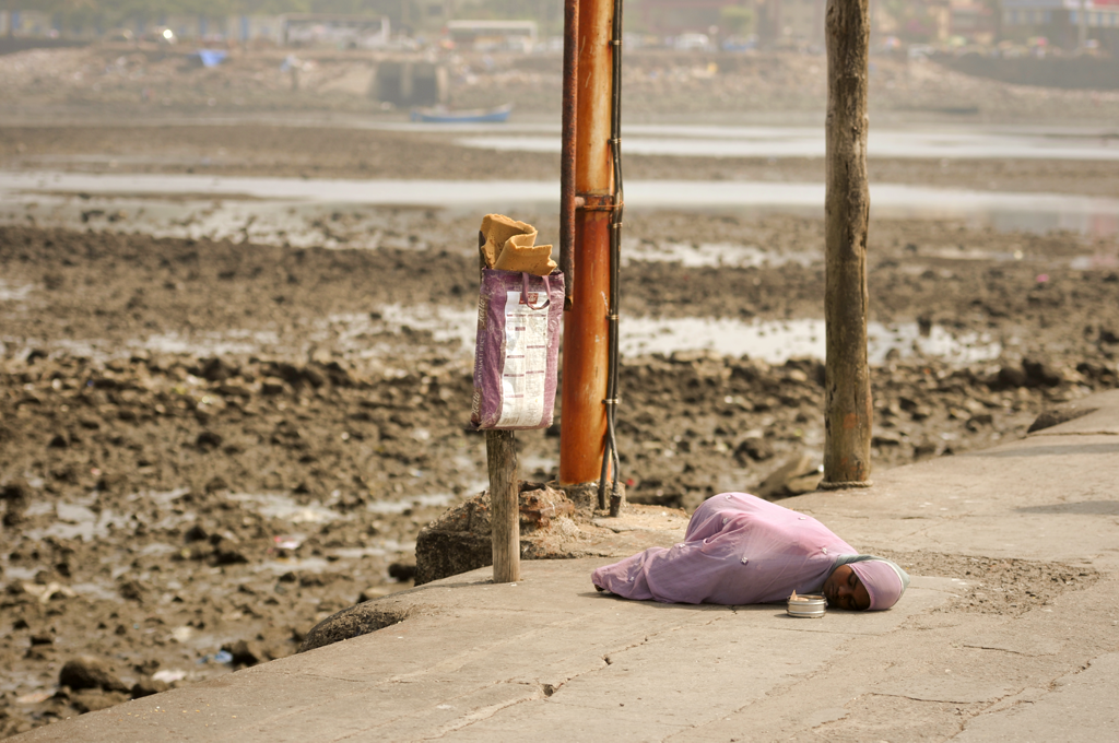 Photo of an Indian girl laying down on the pavement in Mumbai, India.